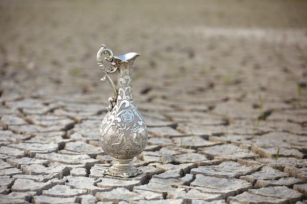 Brocca d'acqua antica d'argento in un deserto secco.