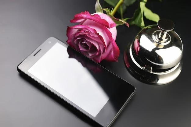 Campanello d'argento e chiave alla reception dell'hotel su sfondo nero