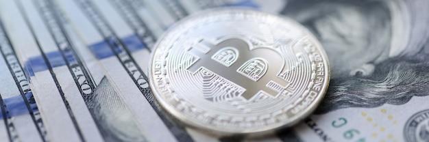 Moneta di bitcoin d'argento che giace su una pila di banconote da un dollaro concetto di scambio di criptovaluta closeup
