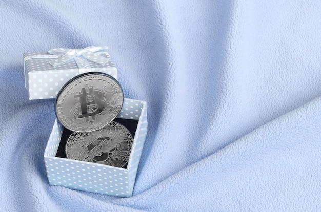Il bitcoin argentato si trova in una piccola scatola regalo blu con un piccolo fiocco su una coperta fatta di morbido