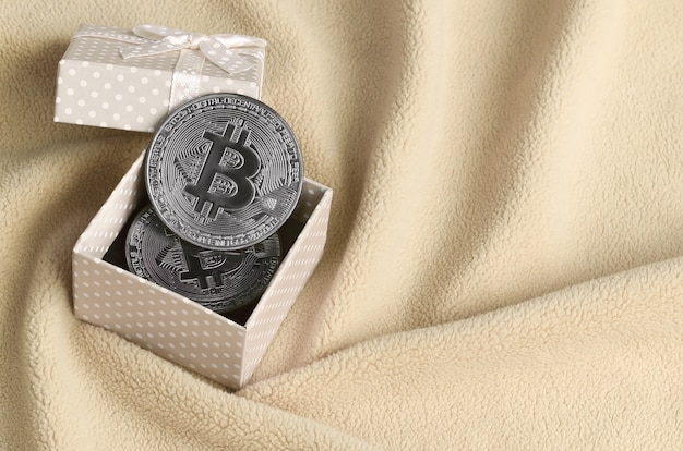 L'argento bitcoin si trova in una piccola scatola regalo arancione con un piccolo fiocco su una coperta