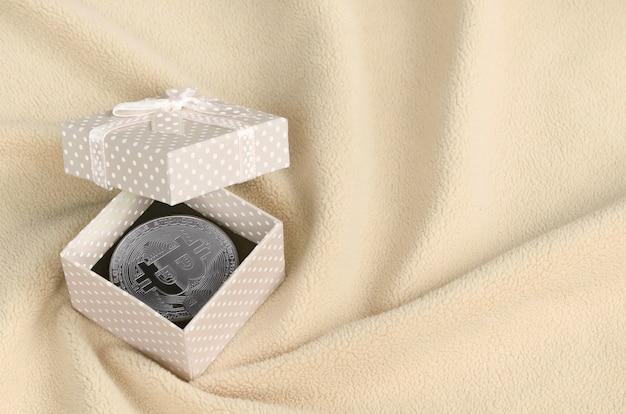 L'argento bitcoin si trova in una piccola scatola regalo arancione con un piccolo fiocco