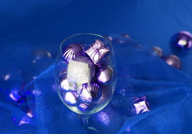 Sfondo di natale argento e blu con decorazioni natalizie in vetro di vite e oro al suo interno. bicchiere di vino con decorazioni natalizie