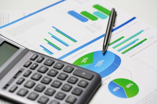 Calcolatore d'argento e statistiche finanziarie sul cuscinetto della lavagna per appunti al primo piano della tavola dell'ufficio. controllo della somma dell'ispettore del servizio di entrate interno che controlla il prestito di risparmio di indagine e il concetto di credito