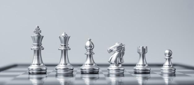 Squadra di figure di scacchi d'argento (re, regina, vescovo, cavaliere, torre e pedone) sulla scacchiera contro l'avversario durante la battaglia