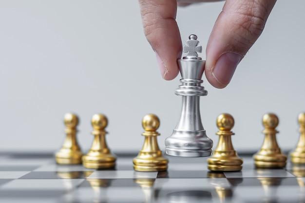 Figura del re degli scacchi d'argento distinguiti dalla massa sullo sfondo della scacchiera.