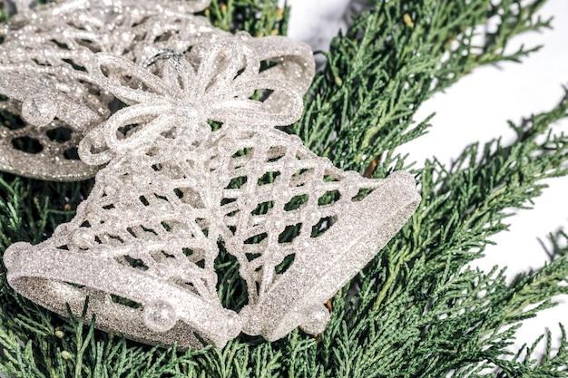 Campana di natale d'argento su un ramo di una conifera, natale, inverno, concetto di capodanno...