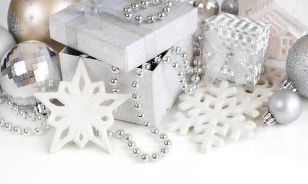 Argento decorazioni natalizie - fiocchi di neve, palline, ghirlande e scatole regalo da vicino isolato su bianco