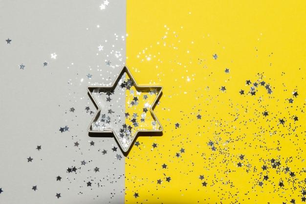 Tagliabiscotti argento a tema natalizio su uno sfondo giallo brillante e grigio con glitter argento e coriandoli a stella