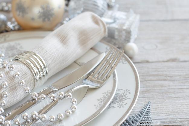 Tavola di natale in argento e crema con decorazioni natalizie