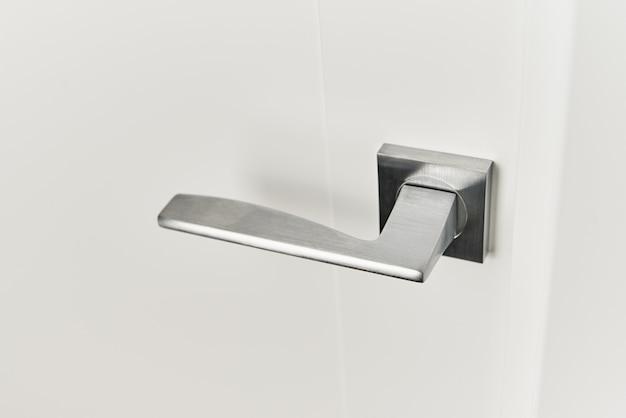 Maniglia della porta d'argento sulla porta bianca. accessori per mobili, elemento interno