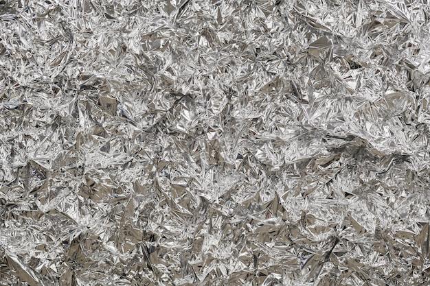 Sfondo in lamina d'argento con superficie stropicciata lucida per lo sfondo della trama