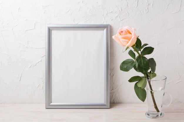 Mockup cornice d'argento con rosa rosa cremoso in vaso di vetro