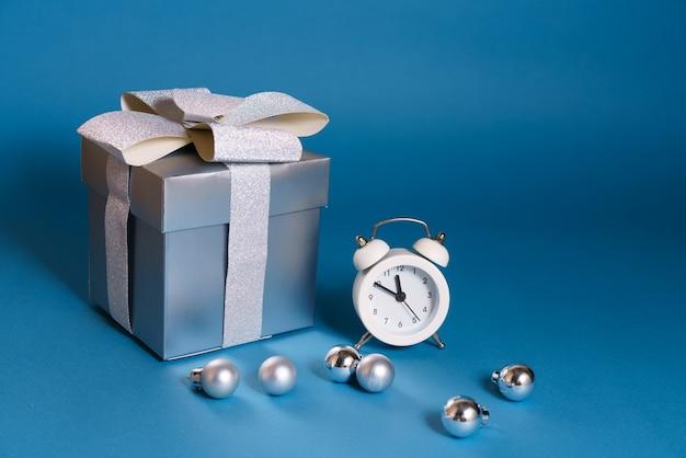 Regalo d'argento con sveglia bianca e decorazioni natalizie su un tavolo blu.