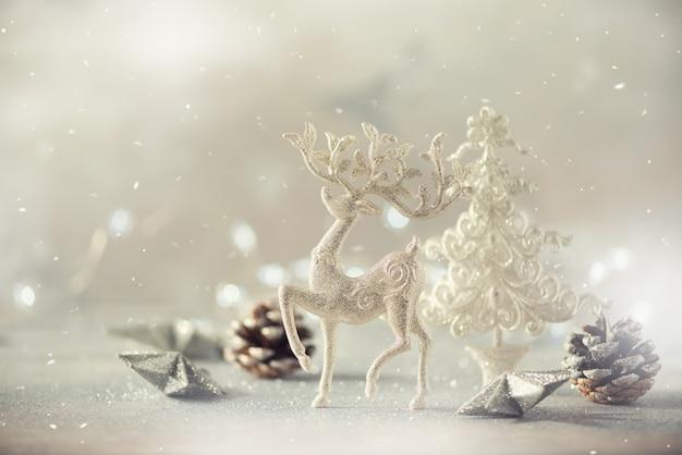 Albero di natale glitter argento, cervi, coni su sfondo grigio con luci bokeh, copia spazio.