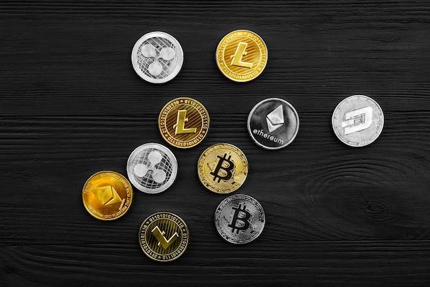 Monete d'argento e d'oro con bitcoin, ripple ed ethereum simbolo su uno sfondo di legno.