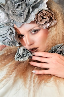 Trucco e manicure beige grigio argento per il modello di ragazze si chiudono con i capelli mossi.