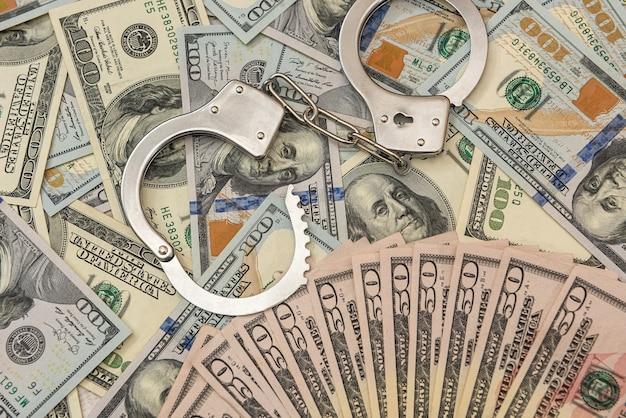 Manette d'argento che giacciono sul dollaro americano, concetto di crimine