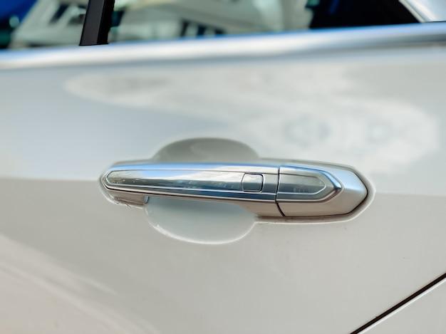 La maniglia d'argento che apre la portiera del passeggero dell'auto in bianco. dettaglio di un'auto da vicino.