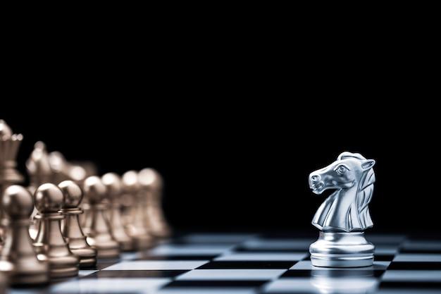 Scacchi del cavallo d'argento incontra il nemico degli scacchi d'oro sulla scacchiera