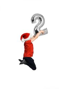 Numero gonfiabile d'argento 2 nelle mani di un ragazzo che salta in un cappello rosso,