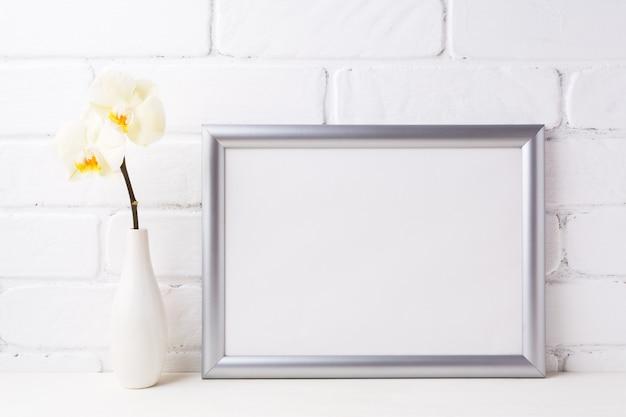 Mockup di cornice d'argento paesaggio con morbida orchidea gialla in vaso