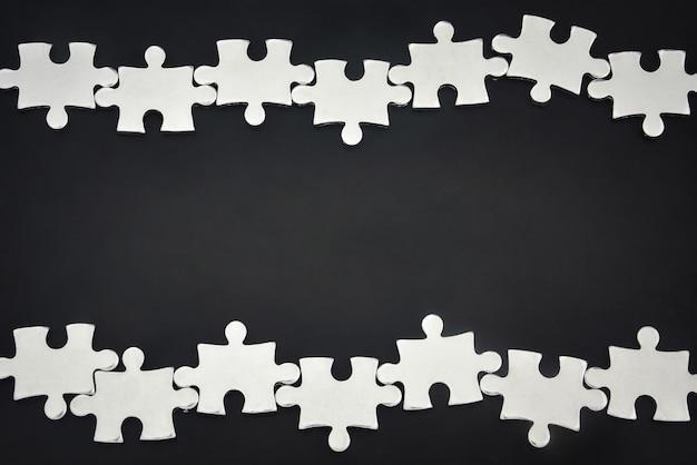 Pezzi di puzzle in metallo argentato disposti come una cornice su sfondo nero concetto di partnership commerciale