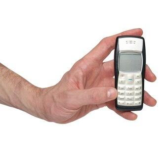 Telefono cellulare d'argento in una mano isolata su bianco