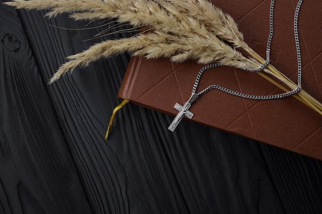 Collana in argento, croce crocifisso e ramo di grano sul libro della bibbia santa cristiana sul tavolo di legno nero, vista dall'alto