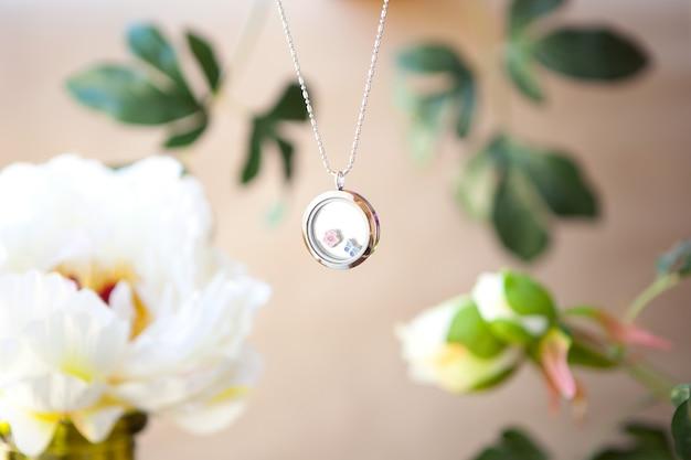 Collana in argento su sfondo di fiori di peonie catene di gioielli di lusso con metallo prezioso in vetro