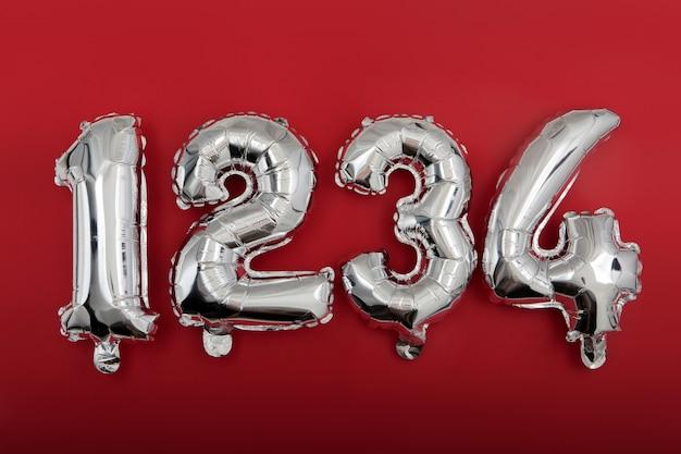 Palloncini con numeri d'argento su sfondo rosso vino