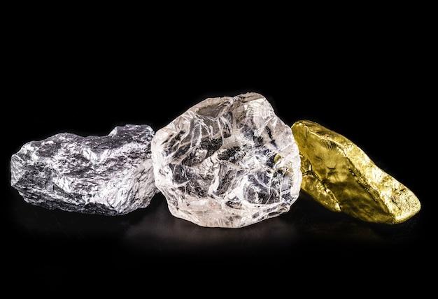 Minerale d'argento, pepita d'oro e diamante grezzo su sfondo nero isolato.