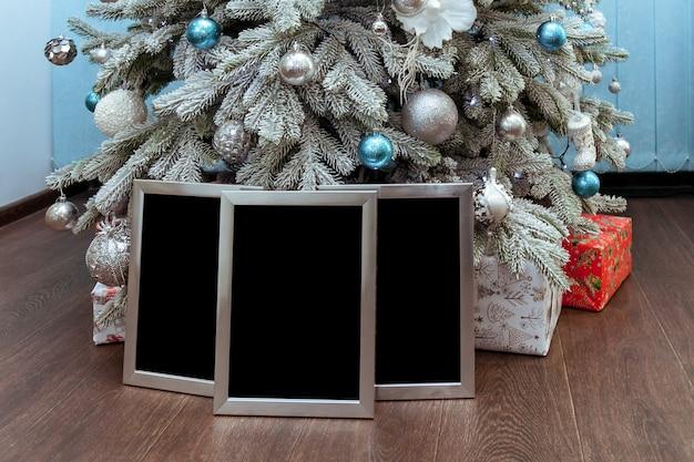 Cornici per foto in argento o certificati sotto l'albero di natale con regali