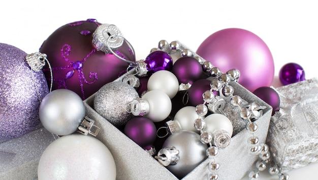 Bordo d'argento e viola degli ornamenti di natale isolato sulla fine di bianco in su