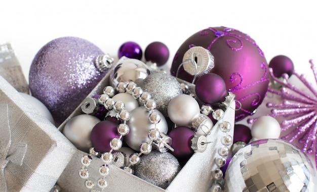 Bordo d'argento e viola degli ornamenti di natale isolato sulla fine bianca su