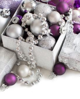 Ornamenti di natale d'argento e viola isolati su bianco