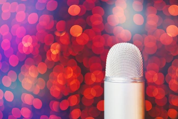 Microfono retrò argento sul palco con sfondo chiaro bokeh primo piano con copia spazio del microfono in conc...