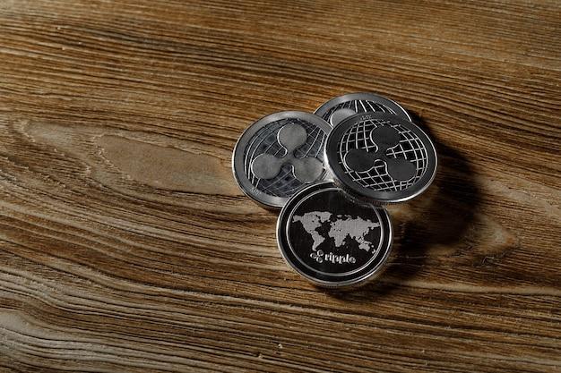 Monete ondulate d'argento su uno sfondo di legno nero