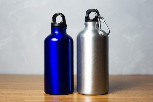 Bottiglia termica blu argento e lucido sulla tavola di legno.