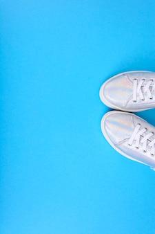 Scarpe da ginnastica argento su sfondo blu con posto per il testo. foto di studio