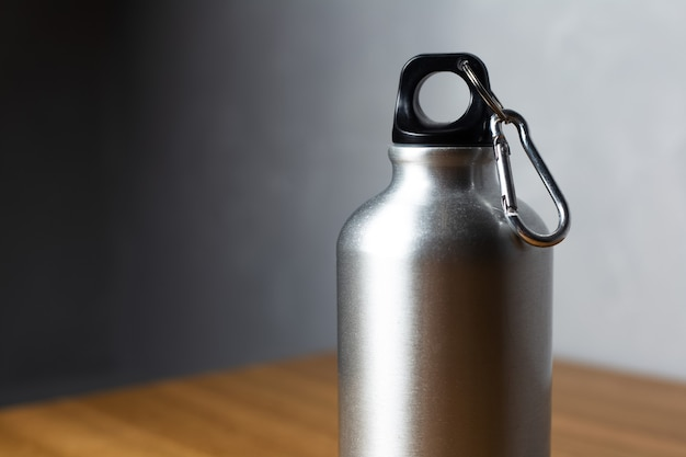 Bottiglia termica d'argento sulla tavola di legno.