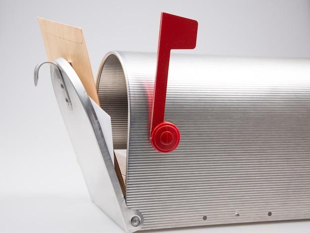 Cassetta delle lettere aperta d'annata d'argento con la busta isolata su fondo bianco