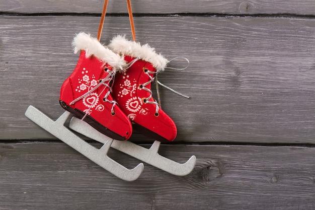 Fiocco di neve d'argento di natale bianco e pattini rossi sopra fondo di legno d'annata. immagine tonica