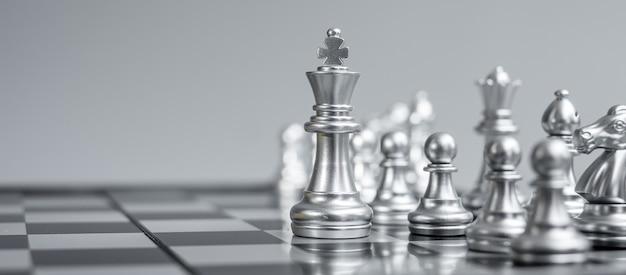 Silverr chess figure team (re, regina, alfiere, cavaliere, torre e pedone) sulla scacchiera contro l'avversario durante la battaglia.