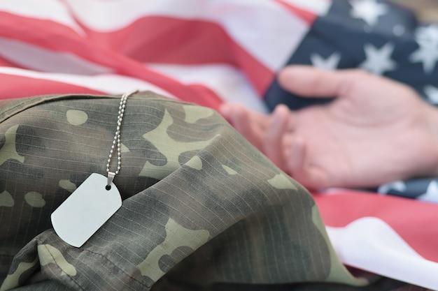 Perline militari argentate con medaglietta e mano di soldato morto su bandiera in tessuto degli stati uniti e uniforme mimetica. ucciso in unità d'azione. concetto di memorial day