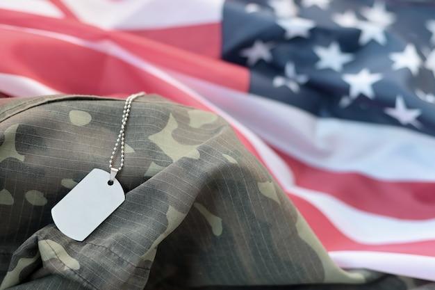 Perline militari argentate con targhetta per cani su bandiera in tessuto degli stati uniti e uniforme mimetica. concetto di memorial day