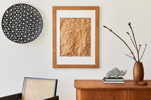 Composizione semplice dell'interno del soggiorno con cornice marrone, comò in legno, libro, decorazioni, vasi ed eleganti accessori personali in un elegante arredamento per la casa.