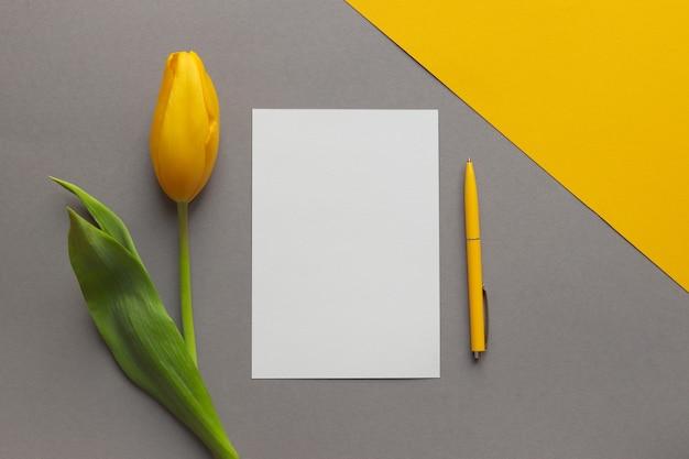 Floreale semplice mock up penna fiore tulipano giallo e carta vuota vuota su sfondo geometrico giallo e grigio