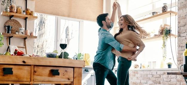 Semplice gioia di amare. integrale di bella giovane coppia in abbigliamento casual che balla e sorride mentre sta in piedi in cucina a casa