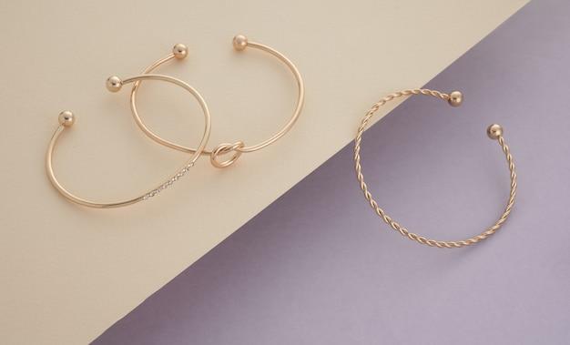 Semplici braccialetti d'oro moderni su sfondo di colori pastello morbidi